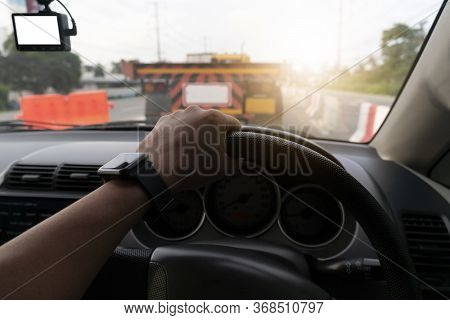 Selective Focus Hand Of People. Driving Inside Car. Blurred Of Traffic Is Slow Due To Road Construct