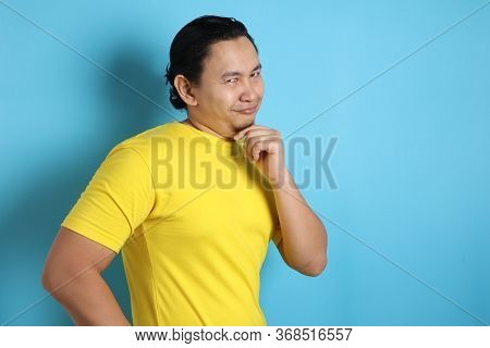 Headshot Portrait Of Funny Attractive Young Asian Man Smiling Flirty And Thinking Something Naughty,