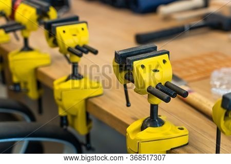 Many Yellow Vises Are Set On The Work Bench At The School. New Grips Or Jaw Vices Fixed At Woodwork