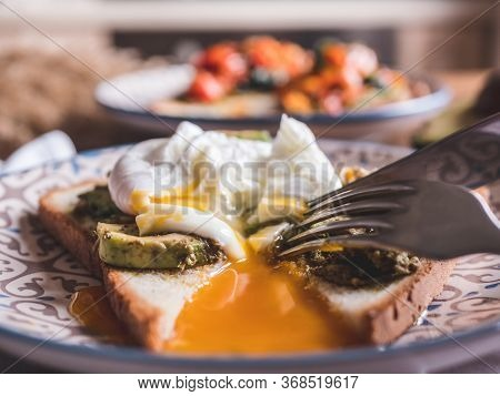 Close-up View Cutting Perfect Poached Eggs With Avocado Paste On Crispy Toast, Fresh Green Avocado S