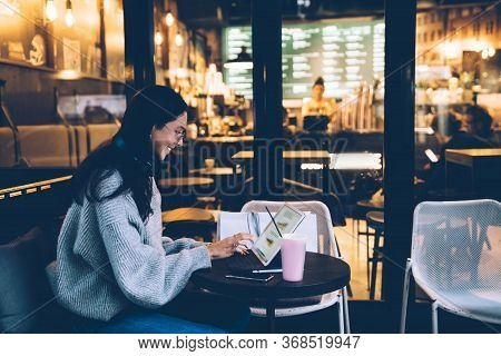 Cheerful Young Woman Browsing Tablet In Cafe