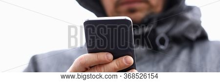 Close-up Of Middle-aged Man Holding Smartphone And Texting Via Messenger. Male In Hood On Street. Fo