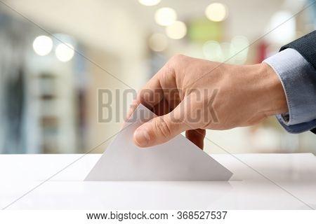 Man Putting His Vote Into Ballot Box Indoors, Closeup