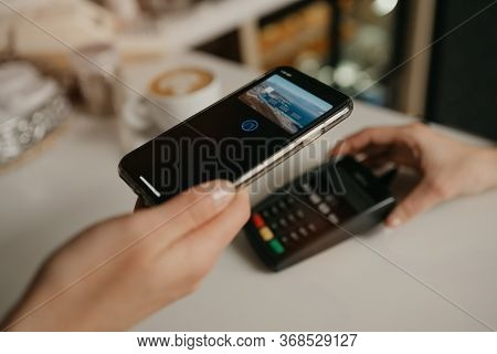 A Lady Paying For Her Latte With A Smartphone By Contactless Pay Pass Technology