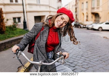 Smiling Female Model With Curly Hairstyle Driving Bicycle Around Town In Autumn Morning. Excited Fre