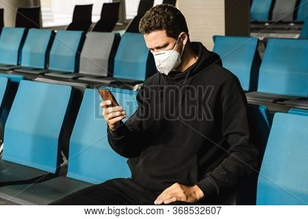 Man In Respirator Mask N95 Is Waiting Next Plane At The Airport And Using Mobile Phone. Coronavirus