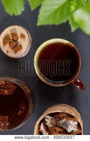 Healing Beverage Of Birch Mushroom Chaga In Ceramic Cup, Mushroom Pieces On Black Backdrop. Chaga Te
