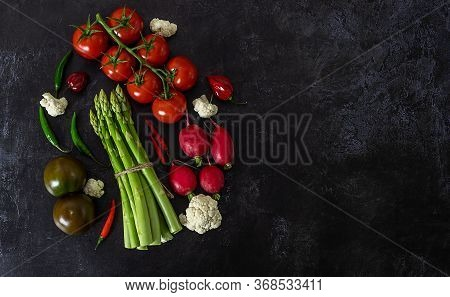 View From Above Of Fresh Raw Vegetables On Black Background. Tomatoes, Peppers, Green Asparagus, Rad