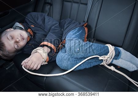Associated Child Prisoner In The Car. Stolen Boy Hostage. Kidnapping And Trade Of Children. Rope On