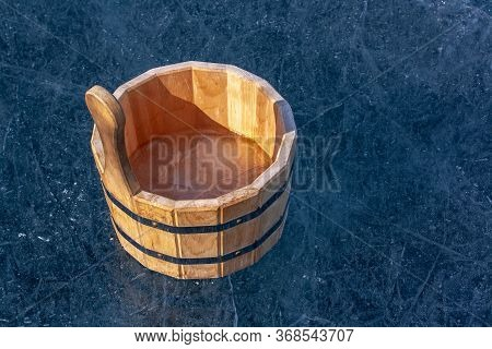 A Wooden Tub With Ice Inside Is Standing On The Ice With Cracks. Iron Tightening Rings Connect Parts