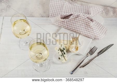 Two Glasses Of White Wine Served With Cheese Board On White Background. Wine Mood Concept.