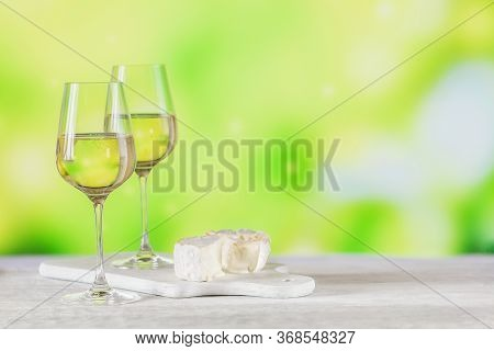 White Wine Served With Cheese Plate On Light Green Background. Two Wineglasses Of Vino Verde. Season