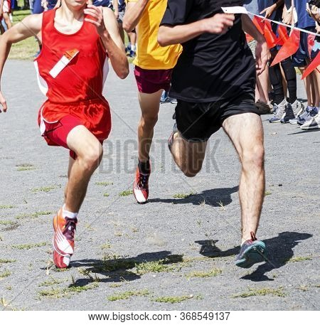 Three High School Freshmen Are Racing The Last Few Meters To Tht Finish Line Of A Cross Country Race