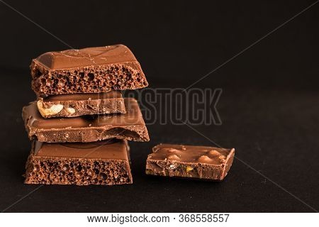 Five Pieces Of Sweet, Milk Chocolate On A Black Background. Brown Pieces Of Chocolate With Nuts Clos