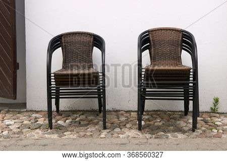 There Are No Visitors In The Street Cafe, The Restaurant Is Closed. Wicker Chairs Stacked On Top Of
