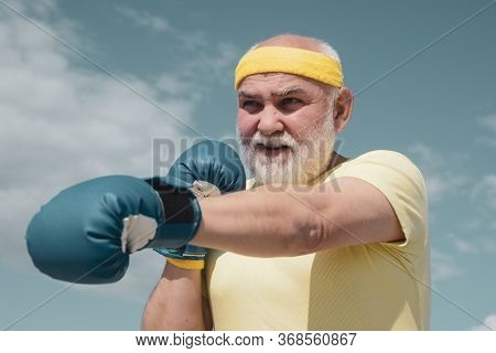 Best Cardio Workout. Elderly Man Hitting Punching Bag. Healthy Fighter Senior Old Man Boxing Gloves.