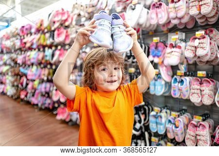 Kid In Supermarket Shoes Shop. Sale, Consumerism And People Concept. Kids Shoes Store In Supermarket