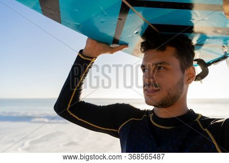 Caucasian man enjoying time at the beach on a sunny day, holding a surfboard above his head with sea in the background