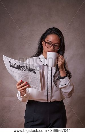 Women Reading A Newspaper With A Cup Of Coffee