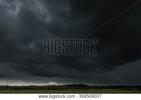 Dark, Swirling, Threatening Clouds In The Sky.\ncloudy Sky Over A Vast, Flat Terrain. These Are Fiel