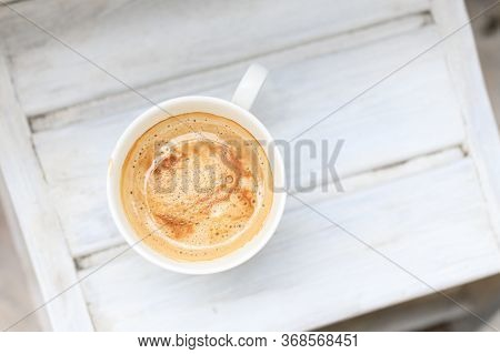 Cappuccino Coffee In A Cup On A White Wooden Table. Top View, Copy Space.