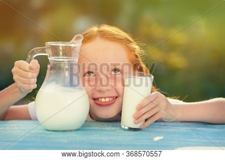 Milk Is Fresh From The Cow - A Beautiful Girl With Dairy Products. Girl Holds Glass With Fresh Milk.