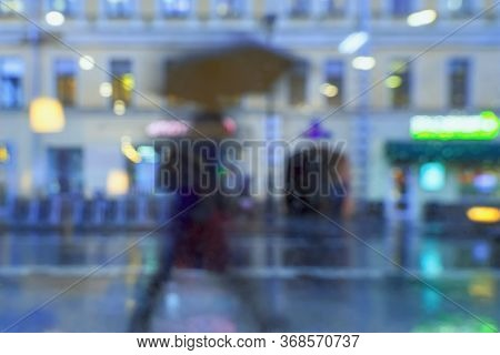 Abstract Blurred Background Of Hurrying Person, Under Umbrella, City Street In Rainy Evening, Bokeh