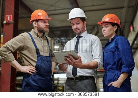 Industrial engineer in formalwear and hardhat discussing machine part with workers using 3D sketch on tablet