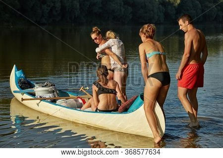 Tokaj, Hungary - Circa 2015: Canoe trip on a river, group of young people about to set off on a journey, summer vacation on river Tisza, Hungary