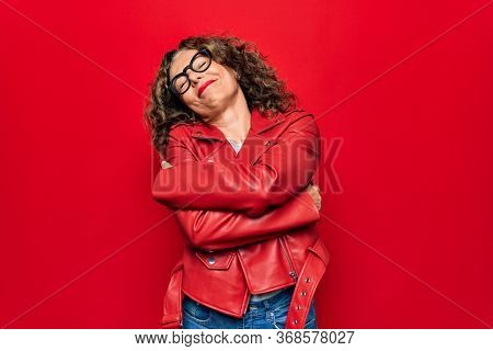 Middle age beautiful woman wearing casual red jacket and glasses over isolated background hugging oneself happy and positive, smiling confident. Self love and self care