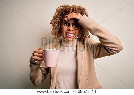Young african american curly woman drinking mug of coffee over isolated white background stressed with hand on head, shocked with shame and surprise face, angry and frustrated. Fear and upset