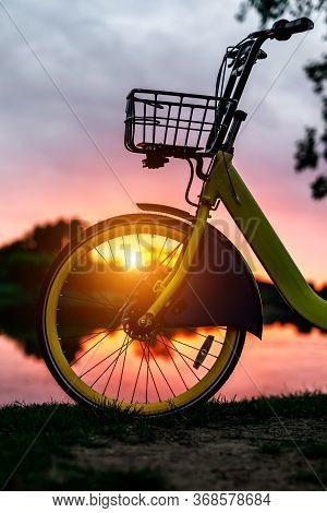 Front Wheel Of A Yellow Bike On The Lake. Sunset.