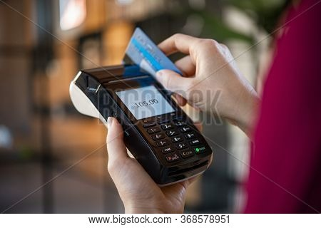 Close up of woman hands making a credit card payment with card reader machine. Credit card swipe through terminal for sale in store. Cashier hand swiping debit card after a purchase.