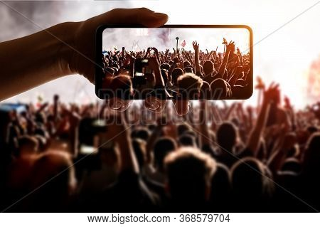 Hand With Smartphone Records Live Music Concert. Using A Mobile Phone At The Show.