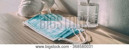 Coronavirus prevention medical surgical masks and hand sanitizer gel bottle dispenser for Covid-19 corona virus protection. Panoramic of PPE.