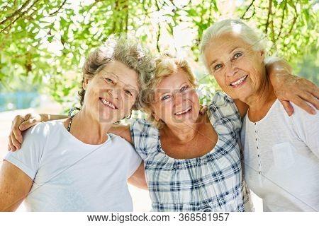 Three happy senior women as best girlfriends in summer in nature