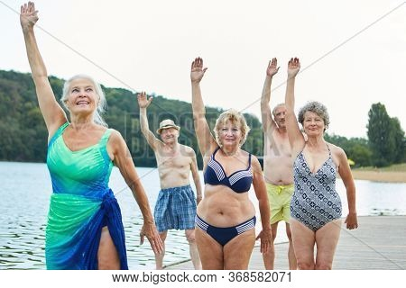 Senior women group doing healthy back training at Rehasport am See in summer