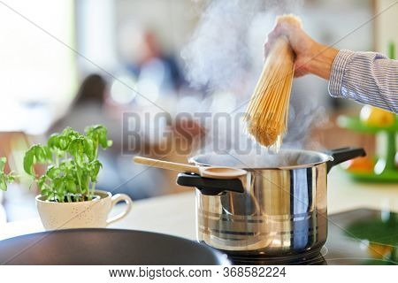 Hand of cook or cook holding spaghetti over saucepan with boiling water