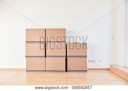 Many moving boxes stacked on the wall when moving to a new apartment