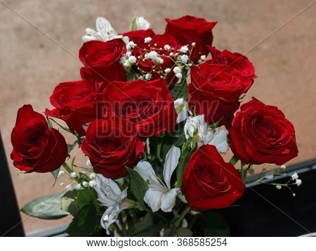 Fresh Red Roses Bouquet With Baby's Breath And White Geranium Flowers In Front Of A Sunny Glass Door