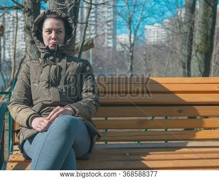 A Young Sad Girl Or Woman Sitting Alone On A Park Bench Feels Depressed And Sad After Quarreling And