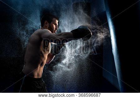 Male Boxer Hitting A Huge Punching Bag At A Boxing Studio. Man Boxer Training Hard.
