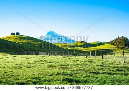 Mount Egmont Snow-capped Between Rolling Green Pastures With Two Water Tanks On Hill, Taranaki New Z