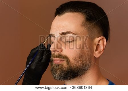 Permanent Makeup For Eyebrows. Tinting Brows. Handsome Man With Eyebrows In Barber Shop. Beauty Proc