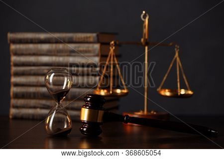 Judges Gavel, Books, Scales Of Justice And Hourglass On Wooden Table. Law And Justice Concept