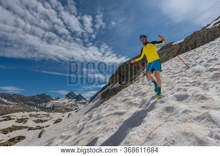 Skyrunner Man Run Downhill On Snow Between Sky And Mountains