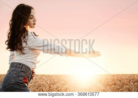 June Summer Sun Solstice Concept With Silhouette Of Happy Young Woman Relaxing Against Warm Golden H