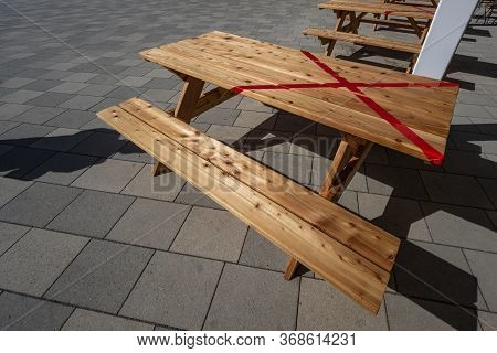 Half Locked Table In A Outdoor Restaurant During The Coronavirus Crisis, Prescribed To Keep The Soci