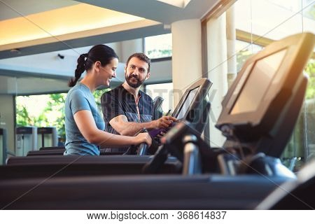 Personal Trainer Working With Client In Gym. Trainer Man Helping Woman With Her Work Out