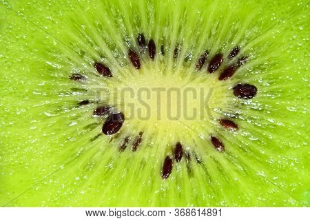 Slice Of Kiwi Fruit On A Full Frame. Fresh Juicy Fruit Slice Closeup.
